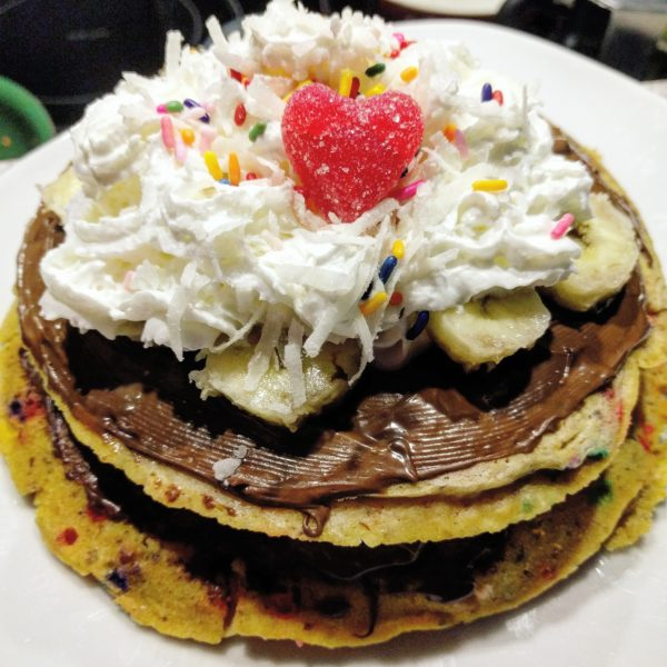 Three Stacked Peanut Butter Banana and Rainbow Sprinkle Pancakes with Nutella and Whipped Cream and Coconut shavings